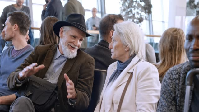 senior man and woman talking at the airport while waiting for boarding - airport terminal stock videos & royalty-free footage