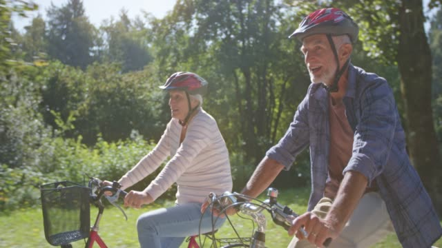 ts senior man and woman talking while riding their bikes through the sunny park - females stock videos & royalty-free footage