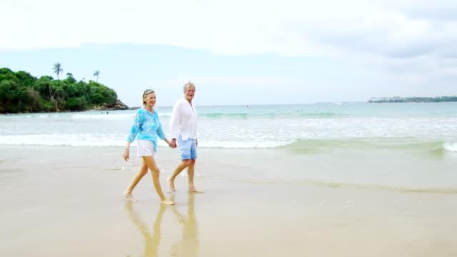 stockvideo's en b-roll-footage met senior man en vrouw lopen op zandstrand hand in hand - 70 79 jaar