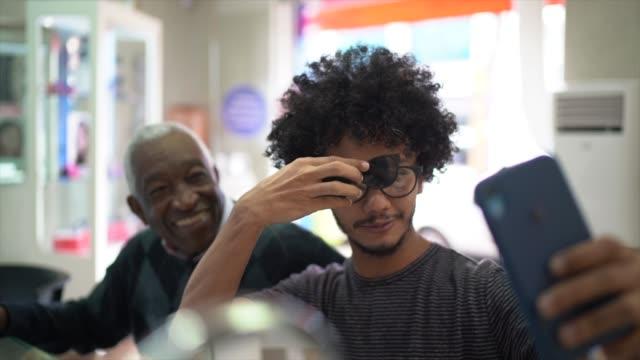 stockvideo's en b-roll-footage met senior man en jonge man het nemen van een selfie/filmen in een optica winkel - lens optisch instrument