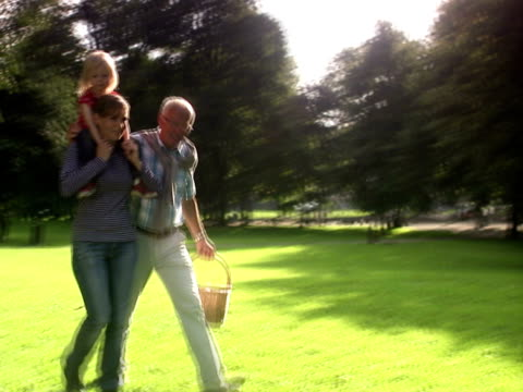 Senior man and young woman carrying a child on her shoulders walking in a park Sweden.