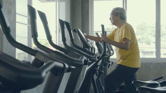senior man asian workout in the gym, elder caucasian do activity exercise for cardio in fitness for healthy on elliptical machine, lifestyle and wellbeing, recreation health and care concept. - cardiovascular exercise stock videos & royalty-free footage