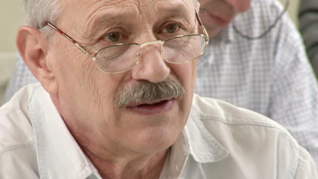 stockvideo's en b-roll-footage met hd: senior man asking question on the seminar - videoportret