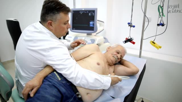 senior man at doctor's office - sistema cardiovascolare video stock e b–roll