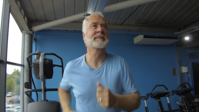 Senior man at gym getting fit jogging on running machine