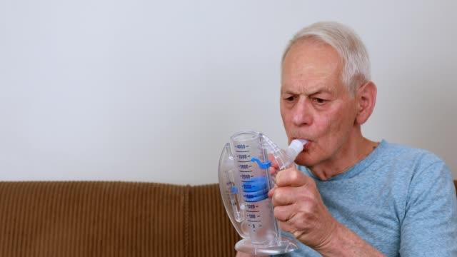 senior man at home using spirometer. 4k - inhaling stock videos & royalty-free footage