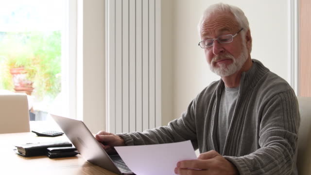 Senior man at home with documents and laptop computer.