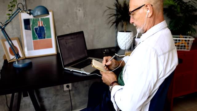vidéos et rushes de homme aîné à la maison, travaillant dans le bureau à la maison - seniornaute