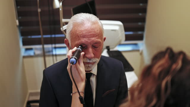 senior man at ophthalmology treatment - lens optical instrument stock videos & royalty-free footage