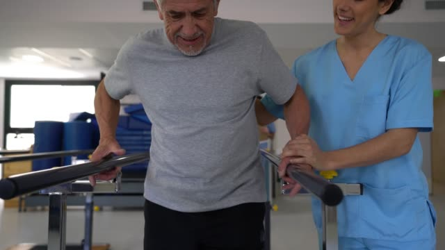 senior man at physiotherapy using parallel bars to walk and therapist standing next to him giving support - recovery stock videos & royalty-free footage