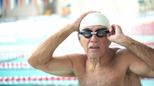 senior man at swimming pool preparing to swim laps - swimming cap stock videos & royalty-free footage