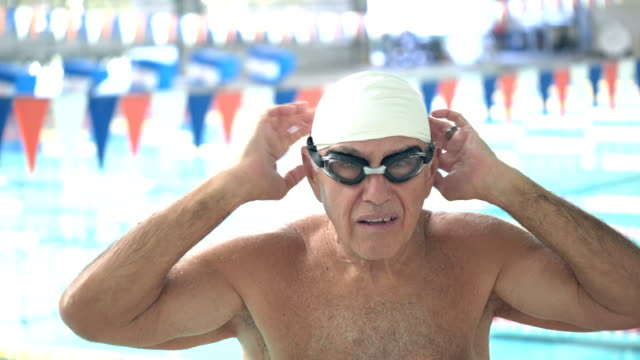 senior man at swimming pool preparing to swim laps - swimming cap stock videos & royalty-free footage