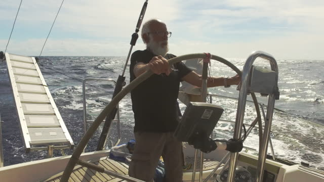 senior man at the helm of a sail boat in a rough sea - balding stock videos & royalty-free footage