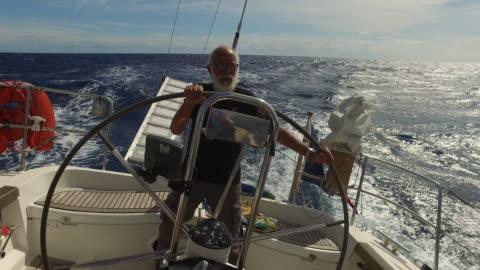 vídeos y material grabado en eventos de stock de senior man at the helm of a sail boat in a rough sea - plano descripción física