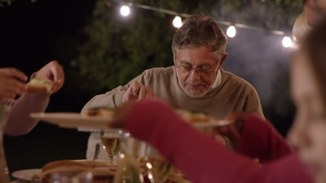 Senior man at the picnic table with his family in the evening