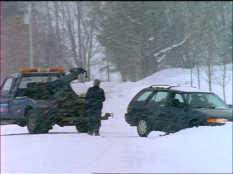 senior man attaching cable from tow truck to station wagon in blizzard - tow truck stock videos and b-roll footage