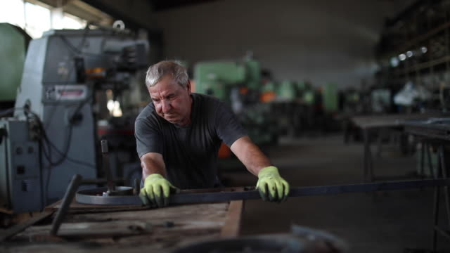 stockvideo's en b-roll-footage met senior man buigen gesmeed metalen hek - metaalindustrie