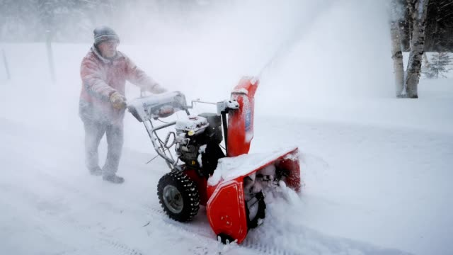 senior man blowing snow in country driveway - deep snow stock videos & royalty-free footage