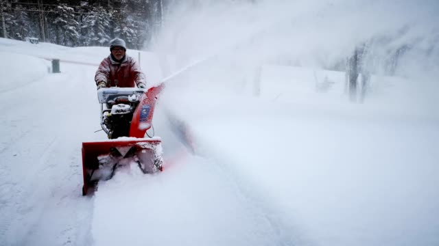 senior man blowing snow in uphill driveway - blizzard stock videos & royalty-free footage