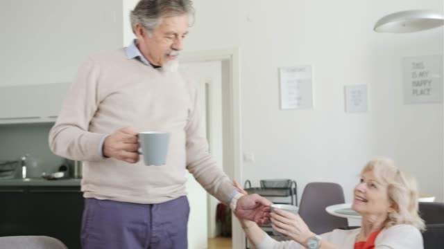 vidéos et rushes de homme aîné apportant une tasse de café à sa femme - 60 64 ans