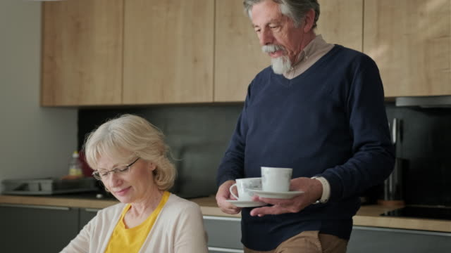 senior man bringing coffee to his wife in the kitchen - wife stock videos & royalty-free footage