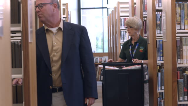 ms ts senior man browses book shelves in library while librarian pushes book cart down aisle / rancho mirage, california, usa - librarian stock videos & royalty-free footage