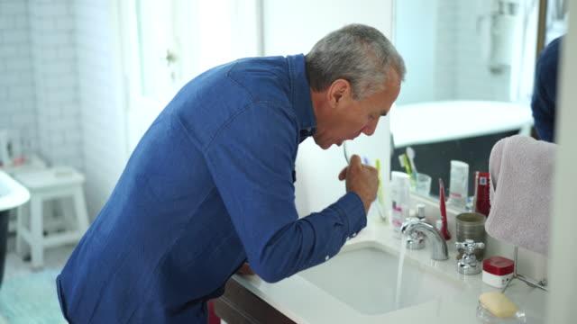 senior man brushing his teeth in bathroom - routine stock videos & royalty-free footage