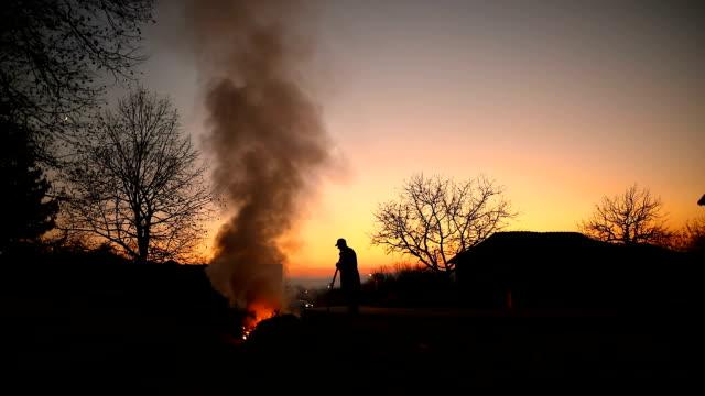 年配の男性が燃焼草し、フィールドでの葉 - 干草用熊手点の映像素材/bロール