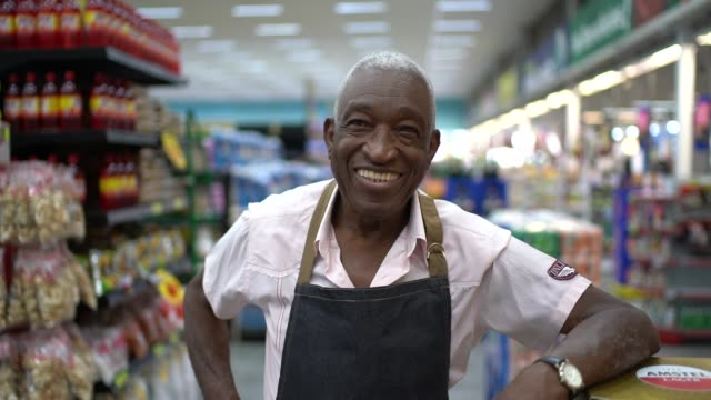 senior man business owner / employee at supermarket - rivolto verso l'obiettivo video stock e b–roll