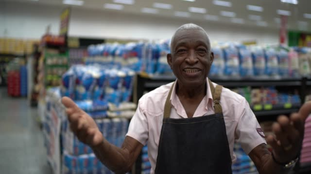 senior man business owner / employee beckoning at supermarket - persuasion stock videos and b-roll footage