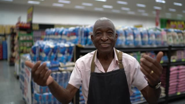 senior man business owner / employee beckoning at supermarket - beckoning stock videos & royalty-free footage