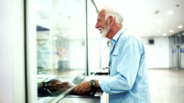 senior man buying a ticket for a ride. - ticket counter stock videos & royalty-free footage