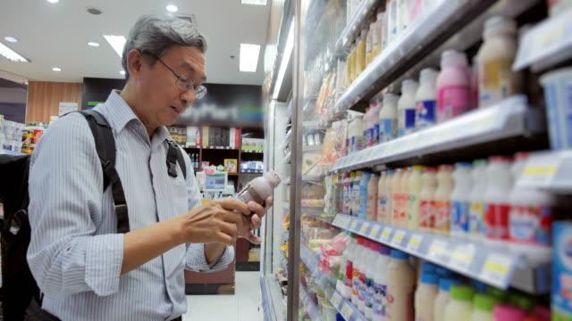 vidéos et rushes de homme aîné achetant la nourriture et la boisson au supermarché. vieil homme faisant des emplettes dans le supermarché local. il tient la bouteille et lit l'étiquette de nutrition. shopping, heureux, personnes, mode de vie, saine et médecine. épiceri - tourisme
