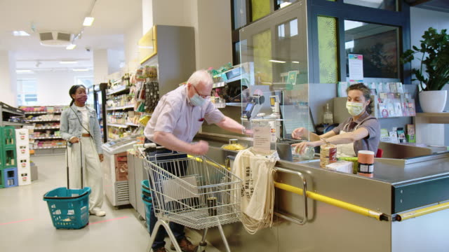 senior man buying groceries in supermarket - germany stock videos & royalty-free footage