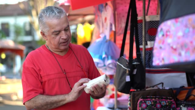 senior man buying on street market - pardo brazilian stock videos & royalty-free footage