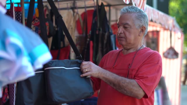 senior man buying on street market - market stall stock videos & royalty-free footage