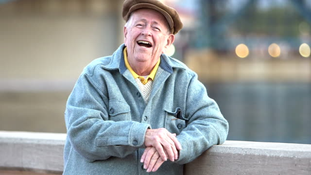 Senior man by waterfront, laughing at camera