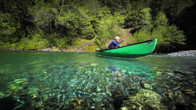 vidéos et rushes de senior man canoeing on river, oregon - canoë