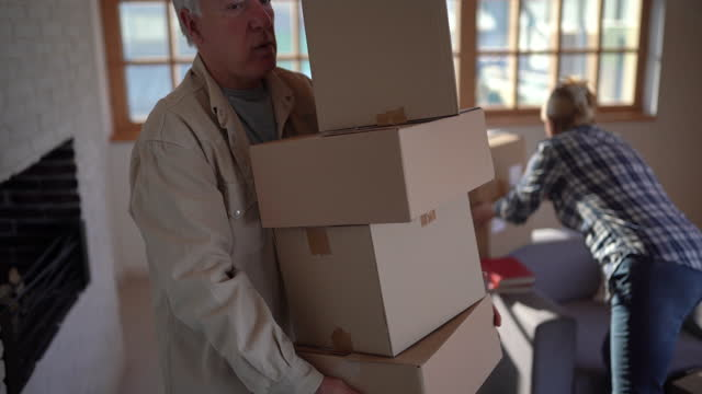senior man carrying cardboard boxes while moving out his apartment - cardboard box stock videos & royalty-free footage