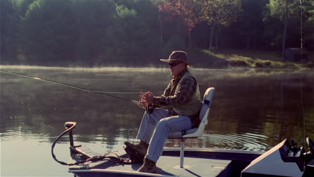 senior man casting fishing line from motorboat - fishing line stock videos & royalty-free footage
