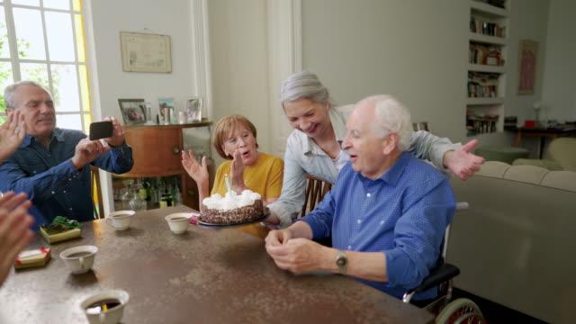 stockvideo's en b-roll-footage met senior man viert verjaardag met vrienden in verpleeghuis - birthday
