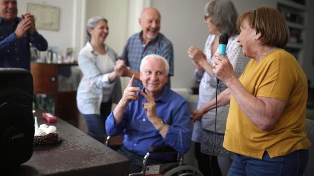 senior man celebrating birthday with friends in nursing home - retirement community stock videos & royalty-free footage