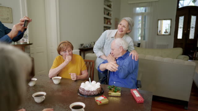 senior man celebrating birthday with friends in nursing home - birthday candle stock videos & royalty-free footage