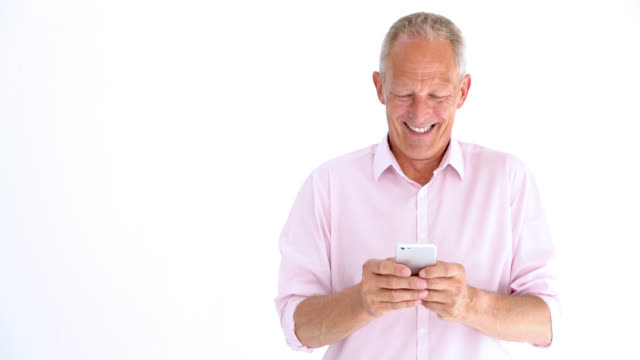 Senior man chatting on his smartphone laughing and smiling