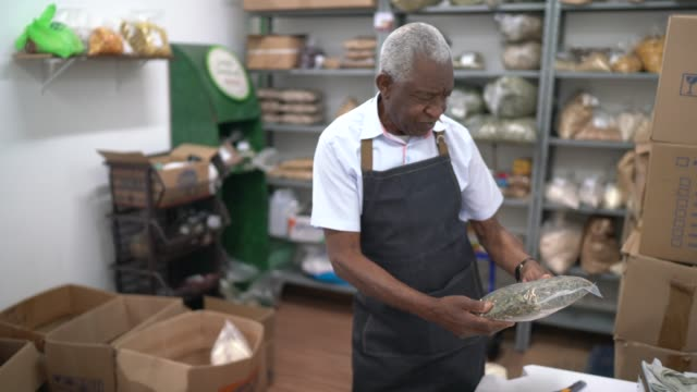 senior man checking the storage room of a natural products shop - pardo brazilian stock videos & royalty-free footage