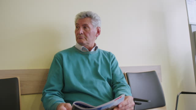 vidéos et rushes de homme aîné vérifiant le temps en attendant à l'hôpital - salle d'attente