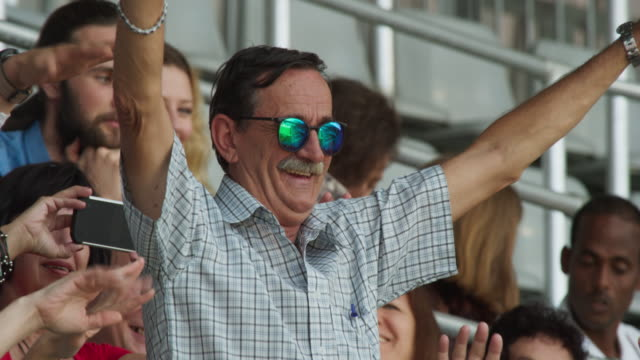 senior man cheering on the stadium tribune - senior men stock videos & royalty-free footage