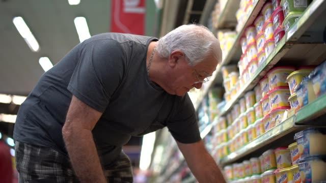 stockvideo's en b-roll-footage met hogere mens die producten in de supermarkt kiest - dairy product