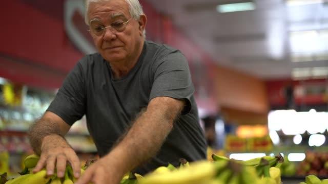 stockvideo's en b-roll-footage met hogere mens die sommige bananen in de supermarkt kiest - markt