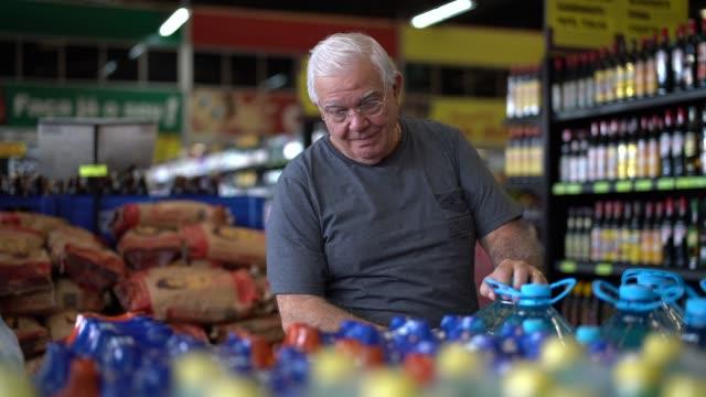vidéos et rushes de homme aîné choisissant quelques produits au supermarché - 65 69 ans